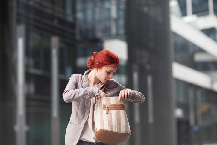 young beautiful business woman holding purse, working in downtown, outdoors