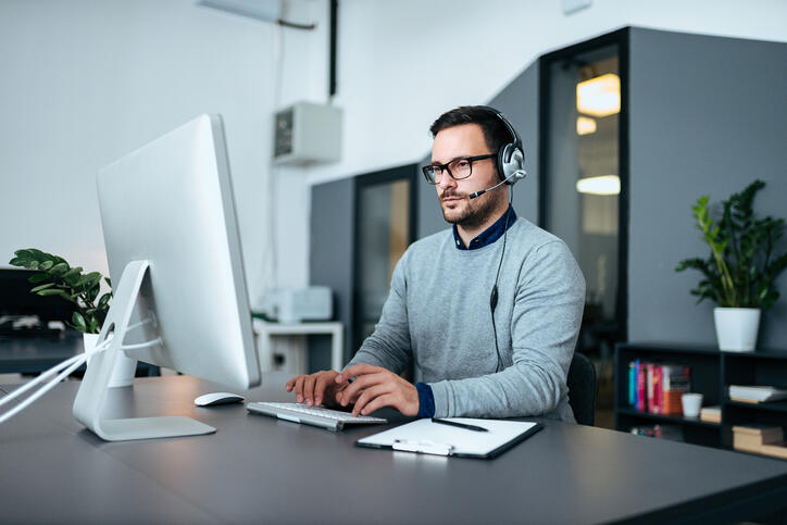 man in gray sweater and glasses sitting at his desk on his computer with a headset on typing on keyboard