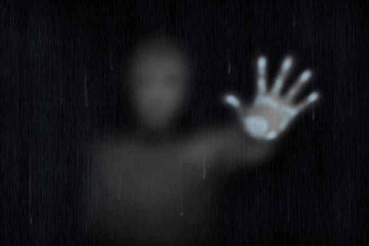 spooky illustration of a ghost with hand pressed on a glass window and a blurred body
