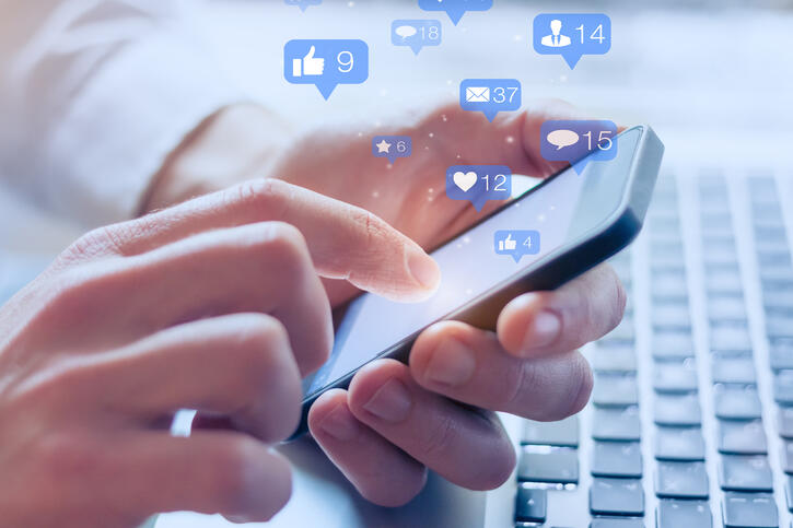Social media interactions on mobile phone, concept with notification icons of like, message, email, comment and star above smartphone screen, person hands holding device, internet digital marketing