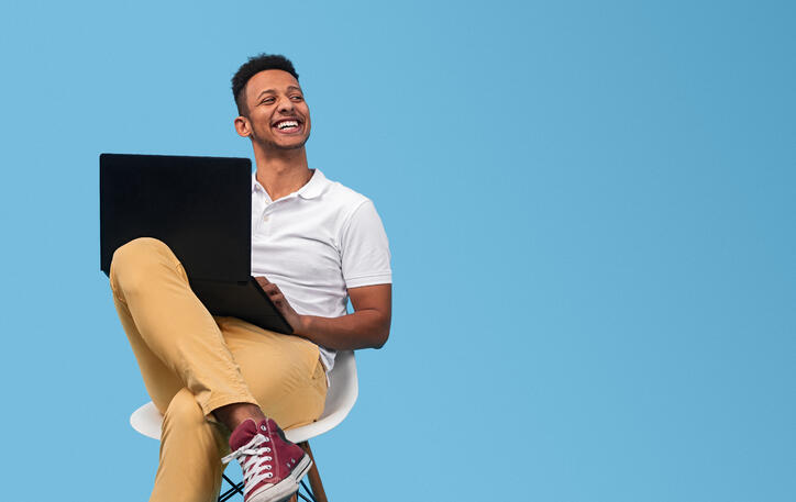 Cheerful black student sitting with laptop on lap smiling and looking away. blue background.