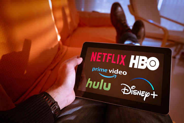 Man holds a tablet with Netflix, hulu, amazon video, HBO and Disney+ logos on screen
