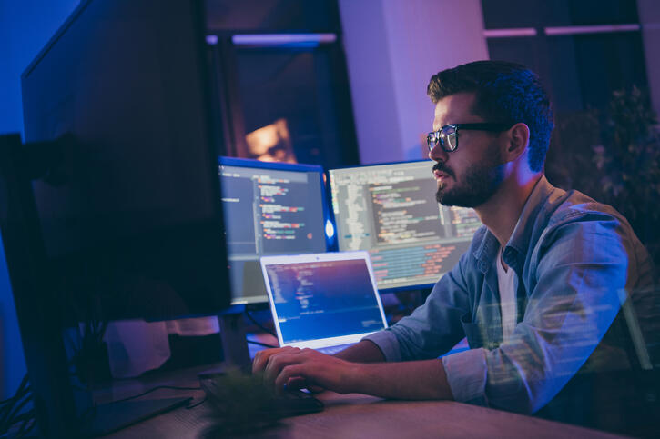 Profile side view portrait of attractive skilled focused guy writing script for ai tech support devops creating digital solution front-end in dark room workplace station indoors