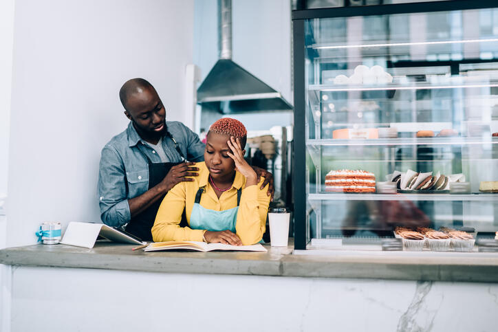 Pensive ethnic adult man consoling sad business partner while working in cafe