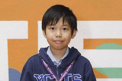 YCIS young mathematician holding a certificate and wearing a medal for mathematics without borders international tournament