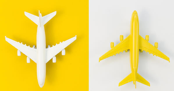 birds eye view of two toy airplanes on solid yellow and white backgrounds