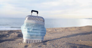 Small suitcase covered by a face mask in the sand by the ocean