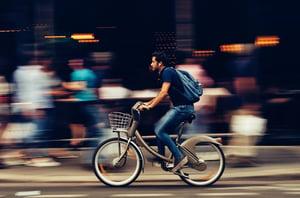man-riding-bicycle-on-city-street-310983