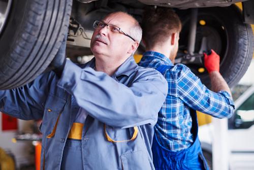 men working on car repairs