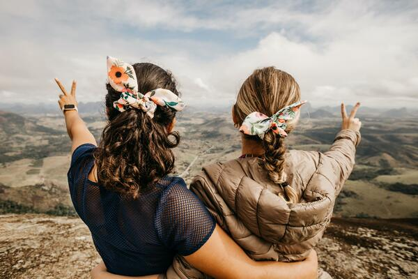 two young women looking into a valley hugging and making a victory sign