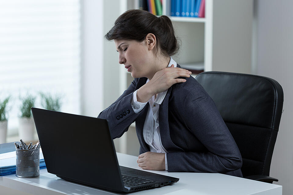 Businesswoman leading sedentary lifestyle causing back pain-1