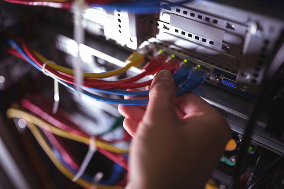 Close-Up of technician plugging patch cable in a rack mounted server in server room