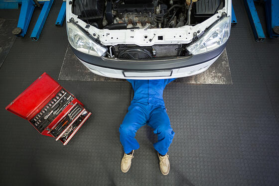 Mechanic lying and working under car at the repair garage