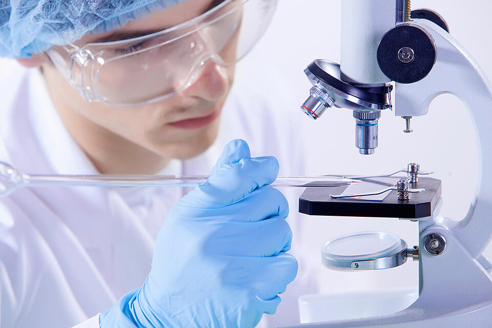 Image of man scientist working in laboratory with microscope