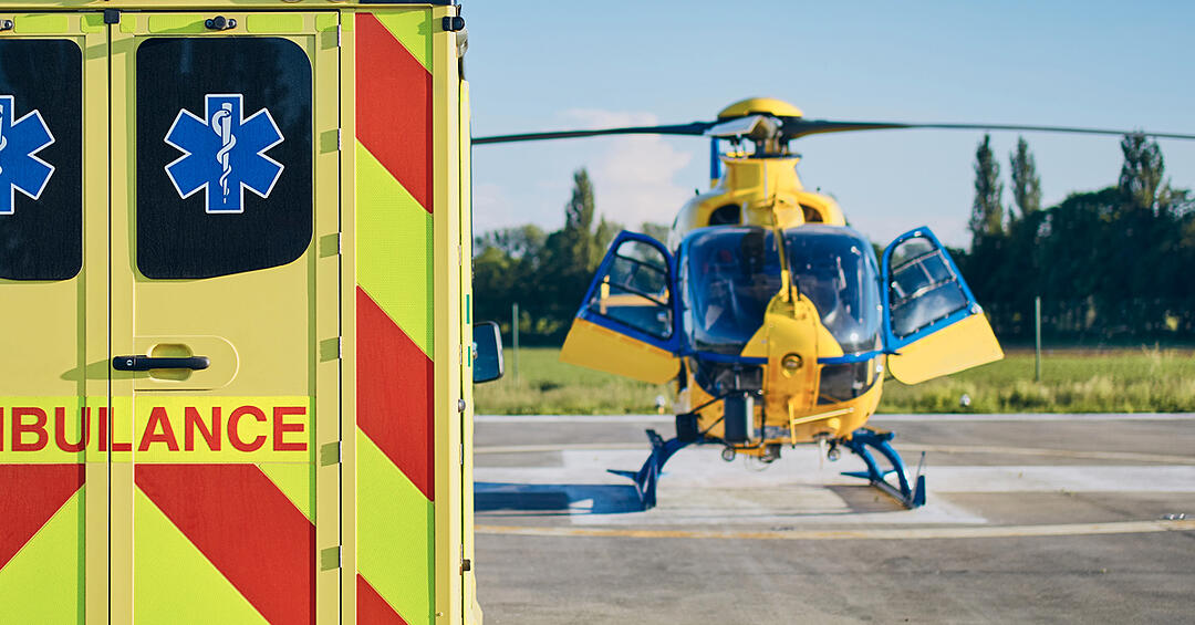 ambulance parked on a helipad beside an emergency helicopter