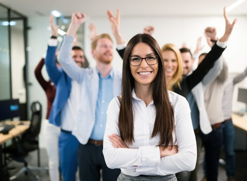Smiling woman in an office with arms folded with colleagues celebrating behind her