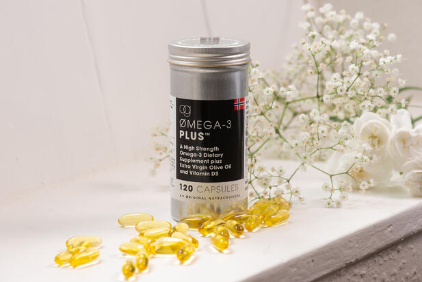 Container of Og Omega-3 Plus capsules with some capsules displayed in front of it and flowers behind