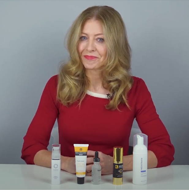Alice Hart-Davis smiling at camera with skincare products on desk in front of her