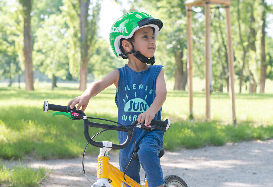 Kind auf gelbem woom 2 Fahrrad