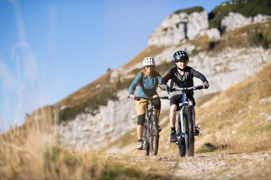 Mutter und Kind mit Mountainbikes im Gelände