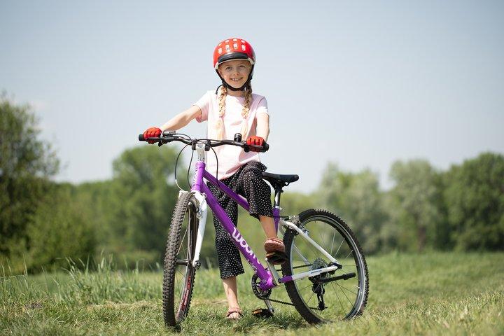 Mädchen mit violettem woom Fahrrad