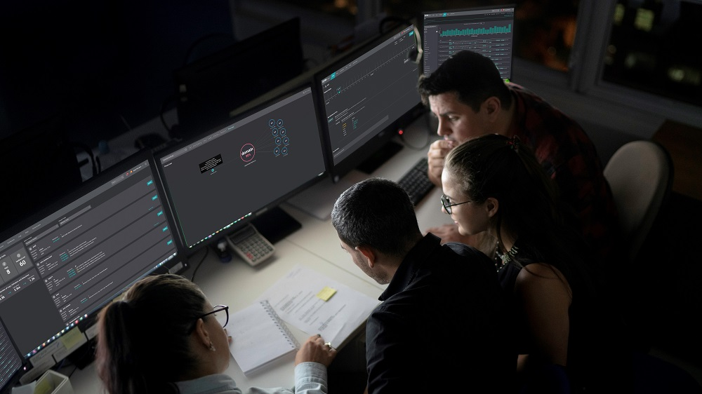 A group of security analysts gathers in front of their monitors to address a threat.
