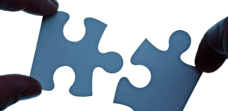 Fingers holding two pieces of a jigsaw puzzle that interlock and fit together.jpeg