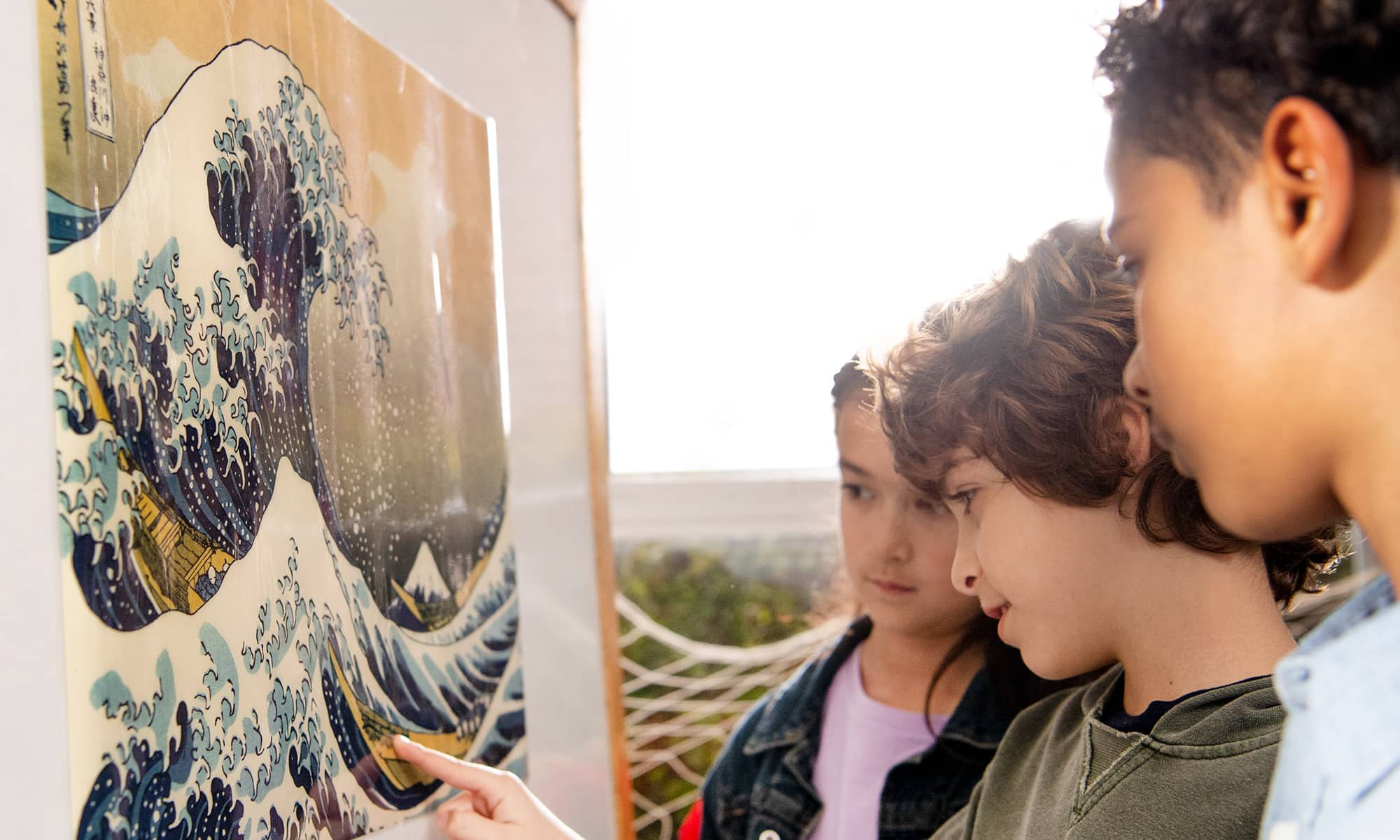 A student points to a detail in the Wave of Kanagawa painting.