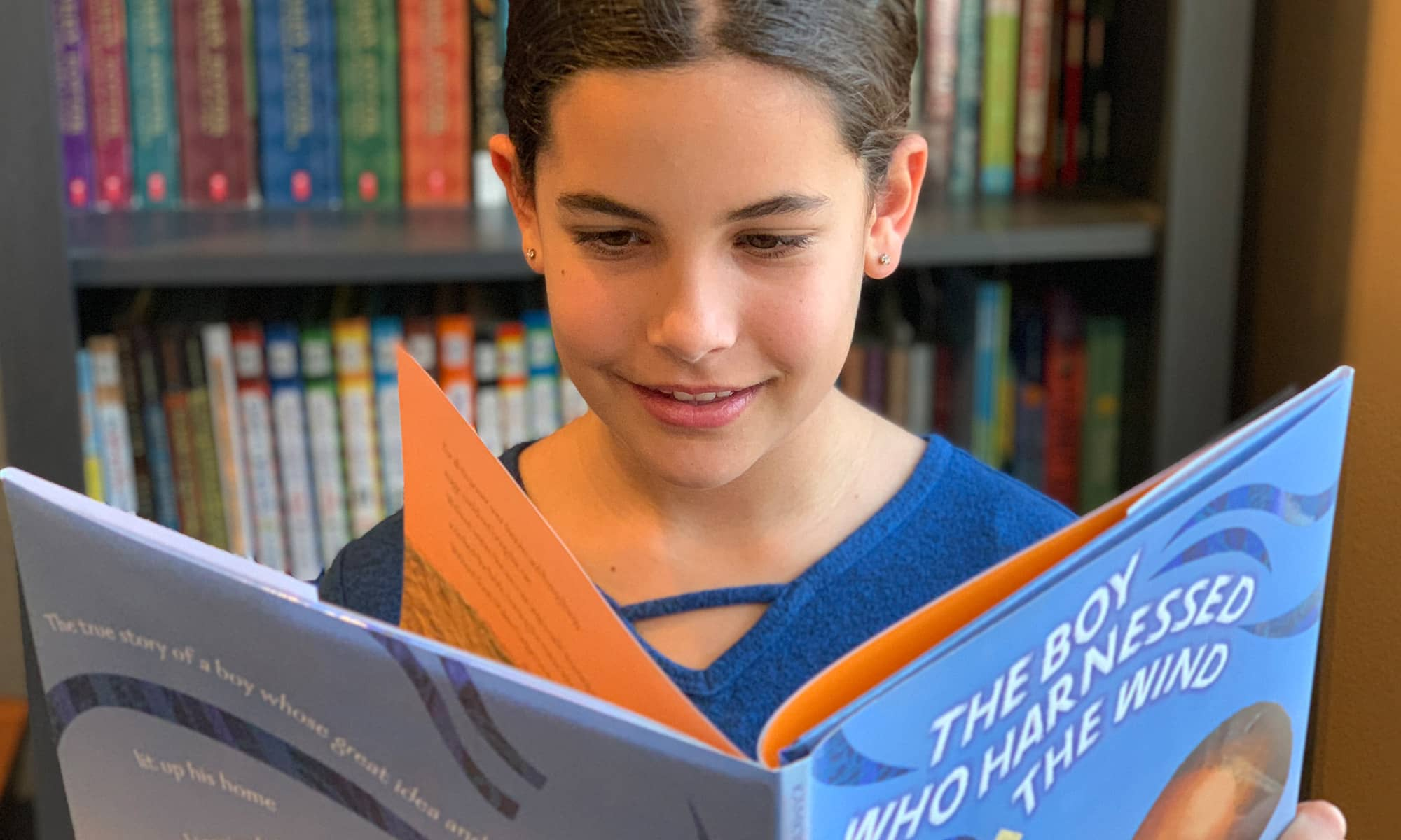 A female student smiles while reading The Boy Who Harnessed the Wind.
