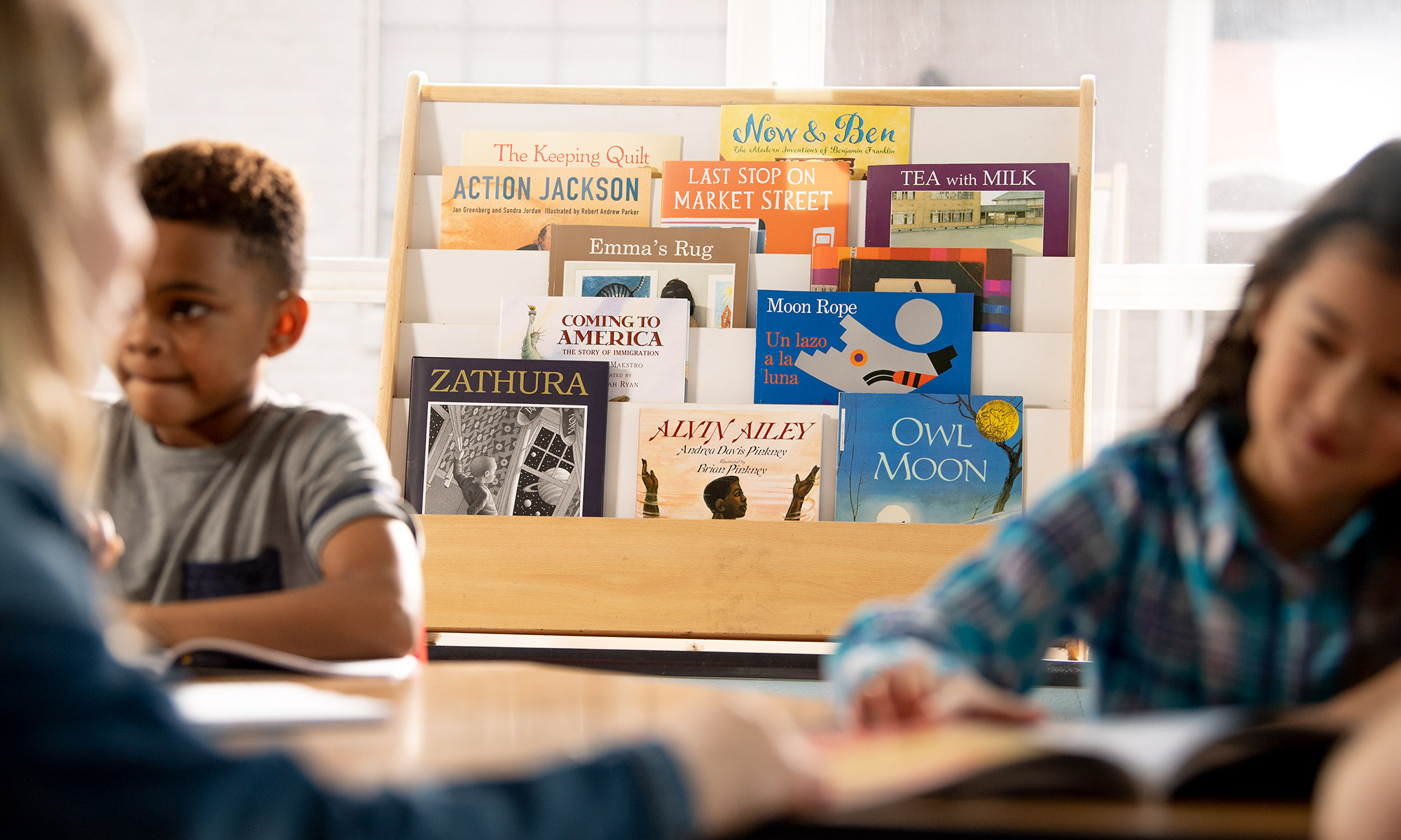 A rack of colorful books sits behind students working.