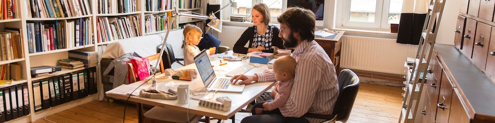 Young couple working from home with small children