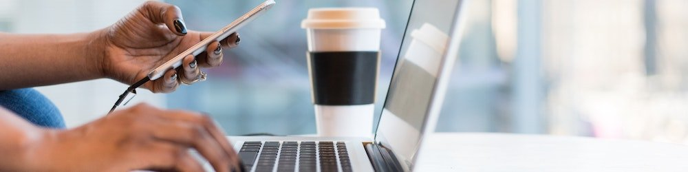 Female hand using her phone and laptop with a cup of coffee