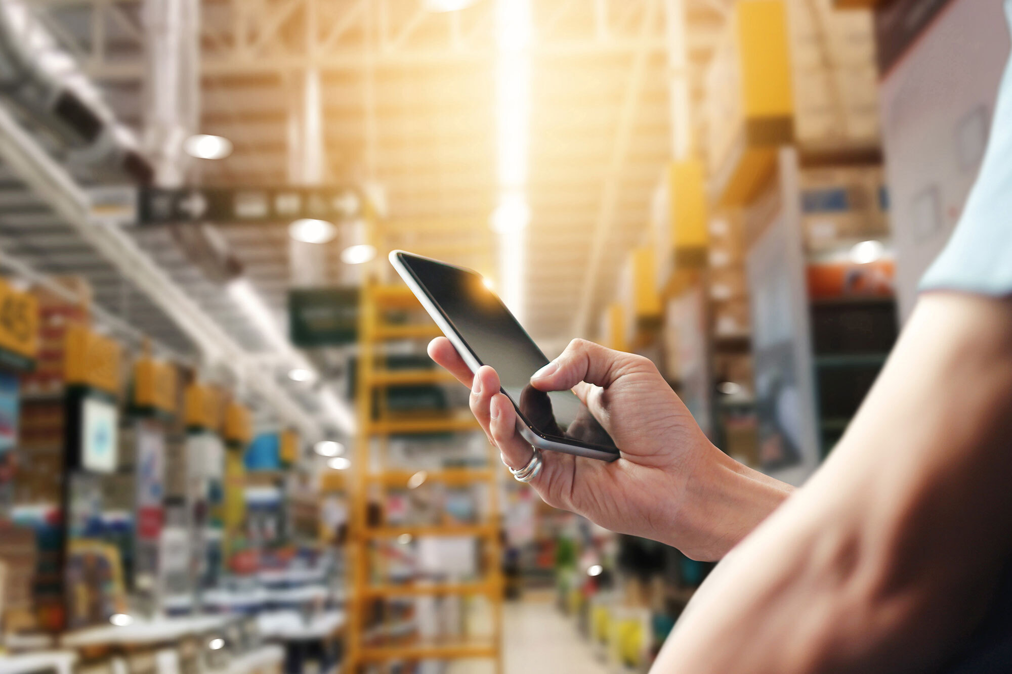 person holding cellphone in fulfillment warehouse